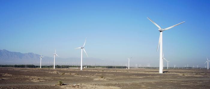 屹立在兩山間的風口處,從高速公路旁綿延到山腳下的風力發電機組