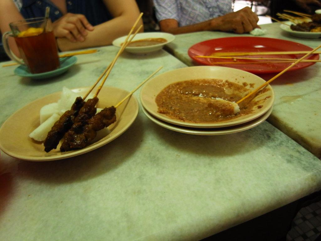 同桌的當地華人阿罵(右上角那隻手)點了盤中那種白白的米製品,看她們一直沾著沙嗲醬吃,我們也點了一盤。因為是指著她們的盤子跟店家點的,阿罵注意到後送了我們三支沙嗲 >3< 還跟我們說這邊的牛肉沙嗲其實分兩種,一種水牛,另一種是別的,還稱讚我們知道來吃這種當地人最愛吃的店 XD